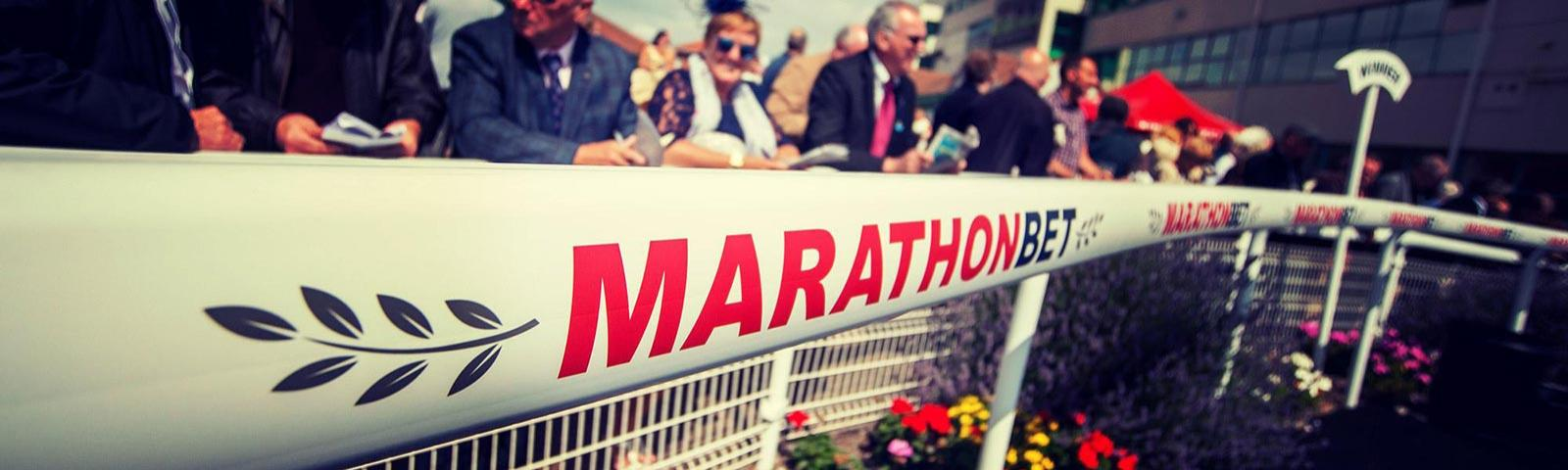 A crowd at Brighton Racecourse behind sponsorship boarding.