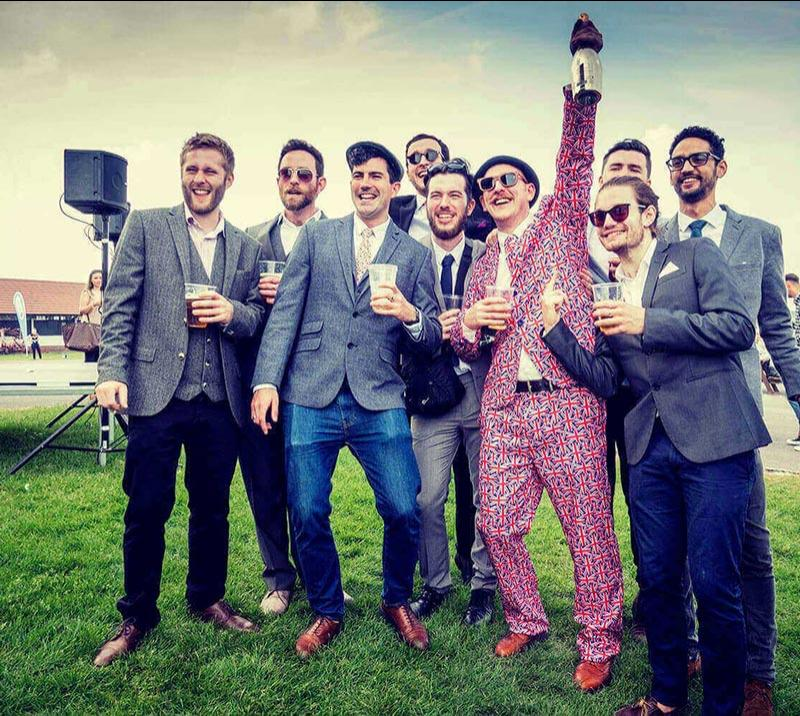 Group of dressed up gentlemen attending races at Brighton Racecourse.