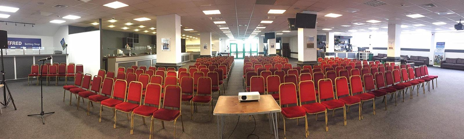 A view of one of Brighton Racecourse' conference rooms fully seated with audio and video equipment ready for guests to arrive