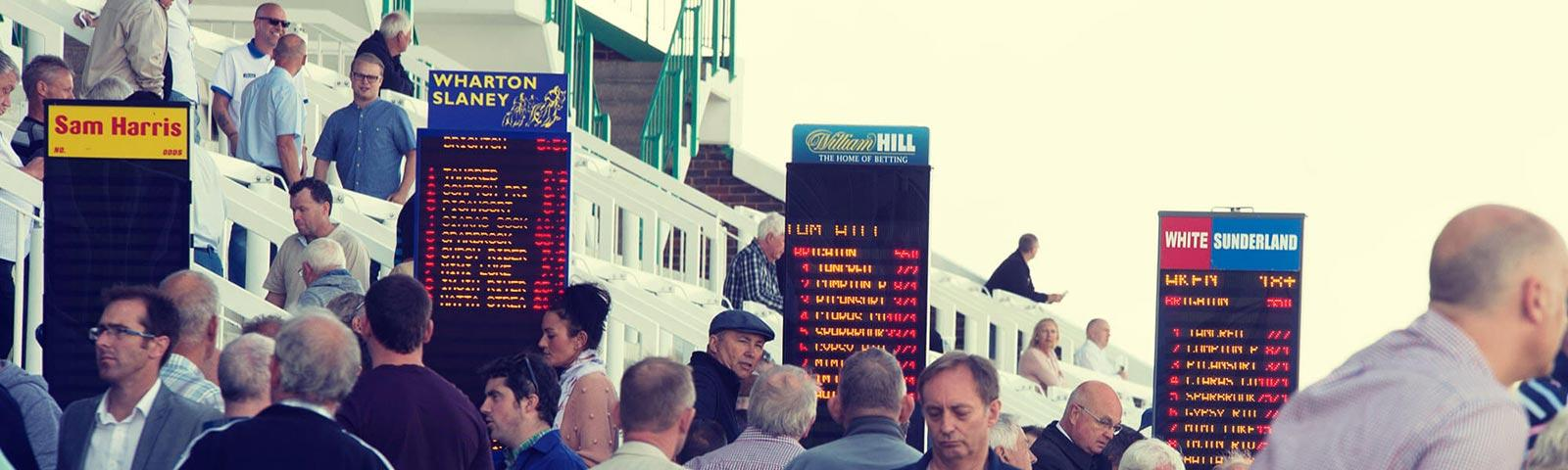 Crowds gathered around bookmakers stands at Brighton Racecourse.