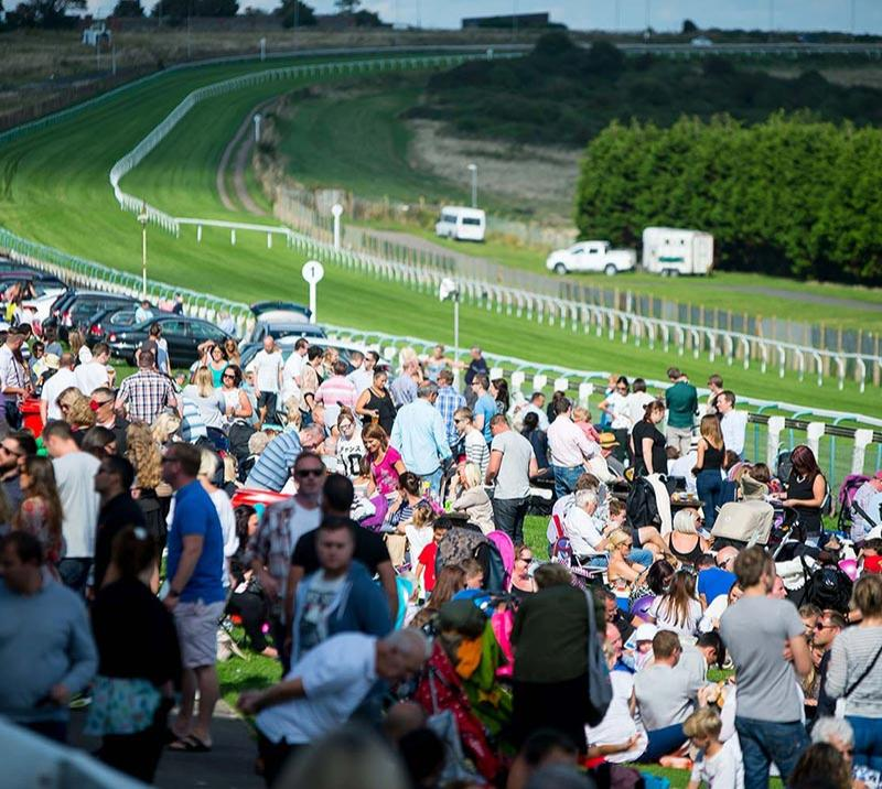 A view of a crowd at Brighton Racecourse on a lovely Summers day.