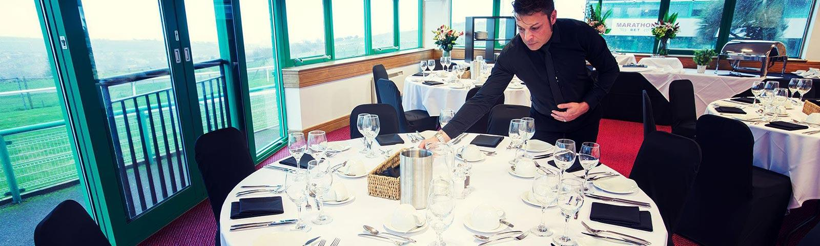 Waiter setting up a large round table